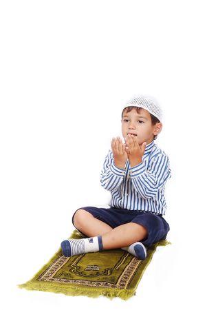 Małe muzułmańskie dziecko modli się w tradycyjny sposób
