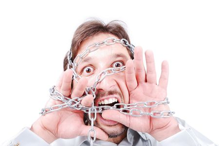 A man with chains on his face and hands screaming photo