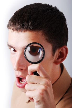 A young man searching with magnifier on eye photo