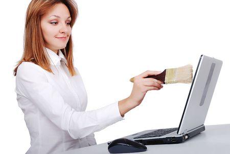 Female model is brushingcleaning her laptop with brush photo