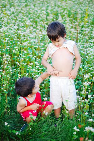 Two little brothers standing outdoor in grass photo