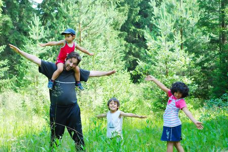 Happy father and three children in nature photo