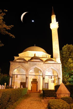 Mosque in night with crescent and star above photo