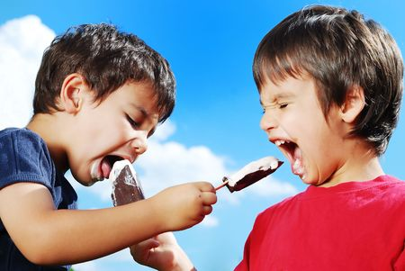 Two kids feeding each other ice cream Stock Photo - 5256694