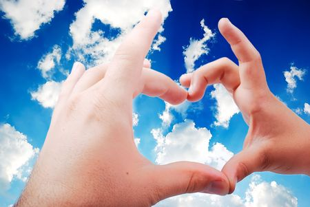 Heart shaped hands in beautiful sky photo