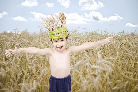 Cute kid in wheat meadow with wheat crown photo