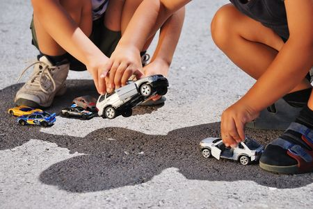 Two kids playing with cars toys photo