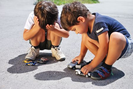 Toys cars in front of children legs photo