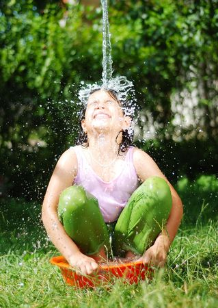 Cute girl is taking a shower outdoor with expression on face photo