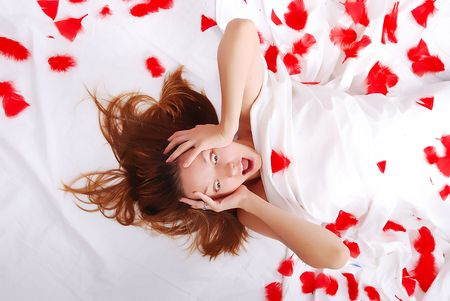 inocent: Beautiful girl laying on bed with white sheets Stock Photo