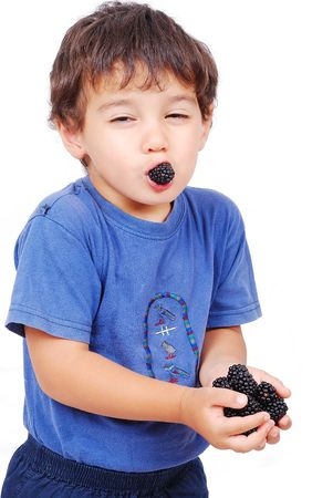 Little cute white kid with blackberry in hands photo