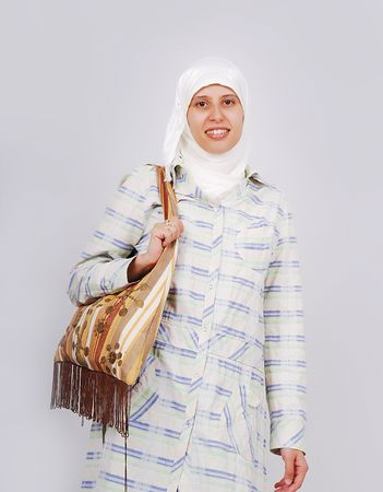 A young muslim woman in traditional clothes with a bag Stock Photo - 5289003