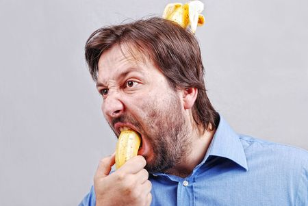 Young man killing himself with a banana Stock Photo - 5289131