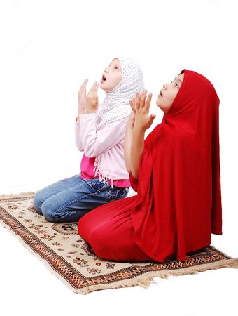 A young muslim girls in traditional clothes praying Stock Photo