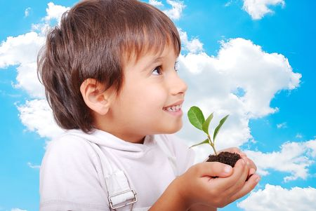 thrive: Little cute child holding green plant in hands