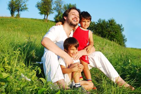 Young father in white with children on beautiful meadow photo