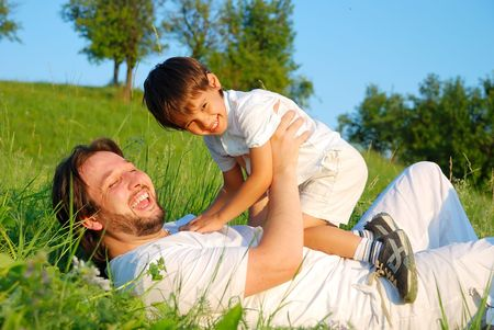 Young father in white with child on beautiful meadow photo