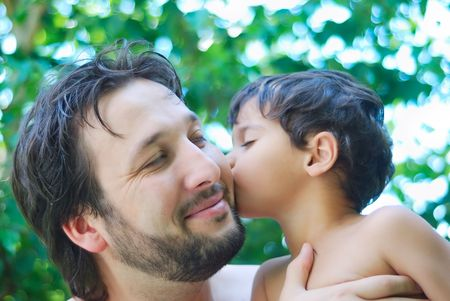 Lovely boy and his father holding him in hands in nature Stock Photo - 5304852