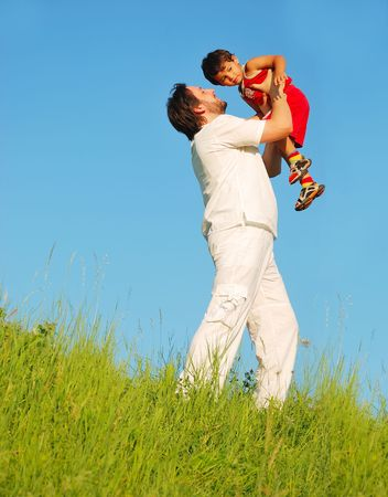 Young father in white with child on beautiful meadow Stock Photo - 5304768