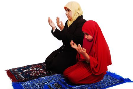 beautiful allah: Young muslim female in traditional clothes praying with little girl