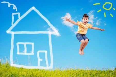 Cute girl is jumping on green meadow with abstract house on photo