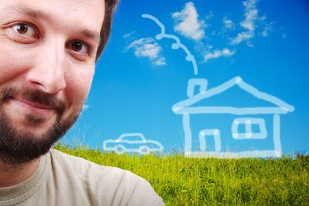 Young male smiling on green meadow with abstract house on photo