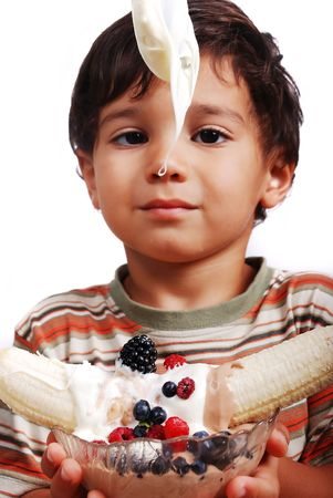 Very cute kid is about to eat very sweet mixed fruint and cream photo
