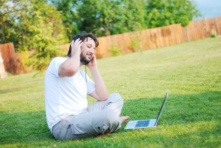 Happy young man on green meadow with laptop photo