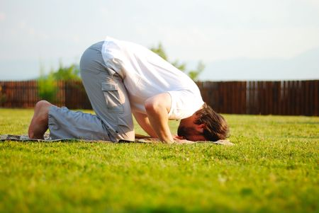 beautiful allah: Muslim male is praying outdoor on green ground
