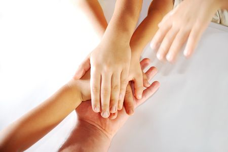 Several children hands together on white background photo