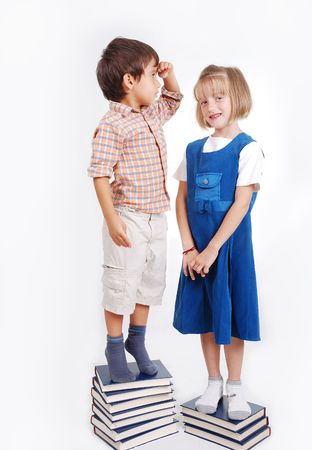 human height: Little cute girl and boy with many books isolated