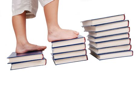 Little legs stepping on books stairs, isolated photo