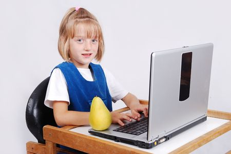 Very cute blond girl with laptop on desk isolated Stock Photo - 5411698