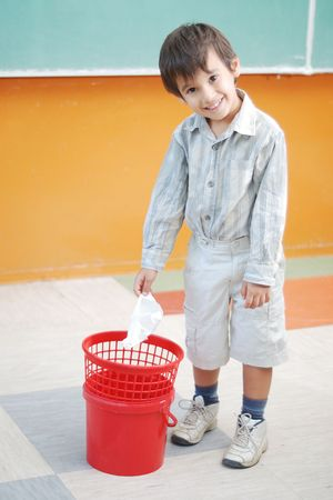 garbage bin: Little cute boy throwing paper in recycle bin Stock Photo