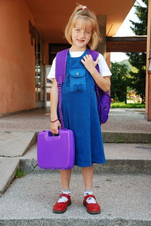 Little cute blond girl with frackles in front of the school photo