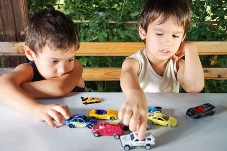 Children playing with cars toys outdoor in summer time photo