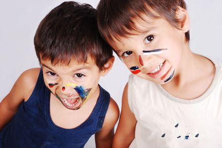 Two little cute brothers with colors on their faces photo