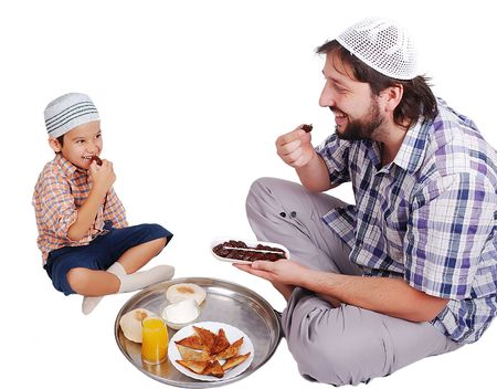 learning pray: Young muslim man and his son with prepared food for iftar in Ramadan