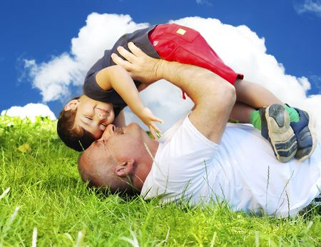 A grandfather and his kid laying and smiling on grass photo