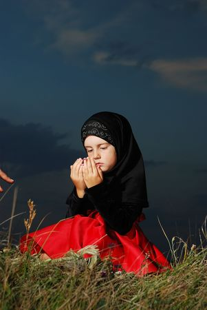 beautiful allah: Little muslim girl on meadow, before sunset Stock Photo