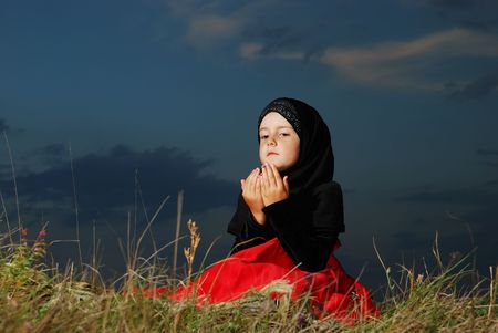 mystery of faith: Little muslim girl on meadow, before sunset Stock Photo