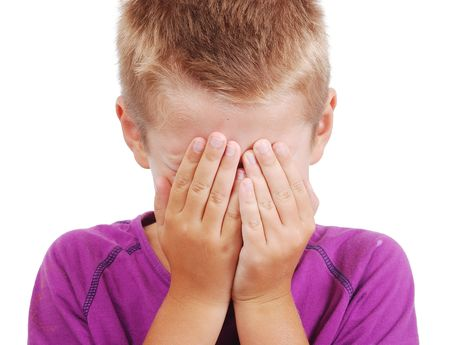 Very cute little boy with sad expression and hands on face