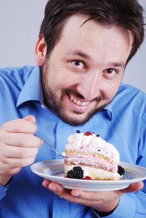 Young man eating colorful cake, isolated photo