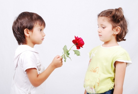 A little cute boy is offering a rose to little girl photo