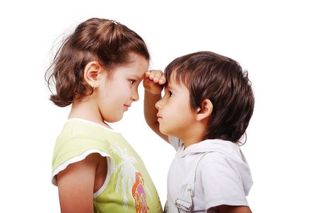 compared: A little cute boy is measuring his height compared to girl Stock Photo