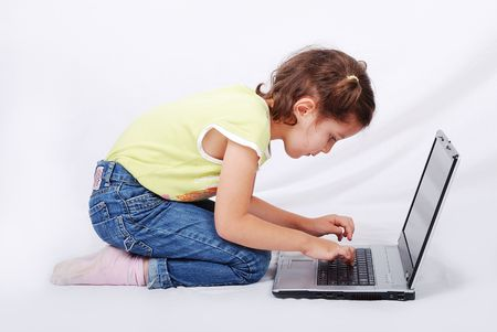 Cute little girl is playing and learning on laptop photo