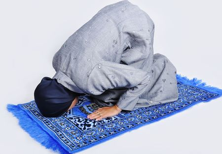 Young muslim woman praying on traditional way photo