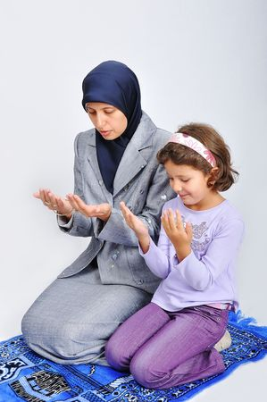 learning pray: Muslim young woman playing with her daughter