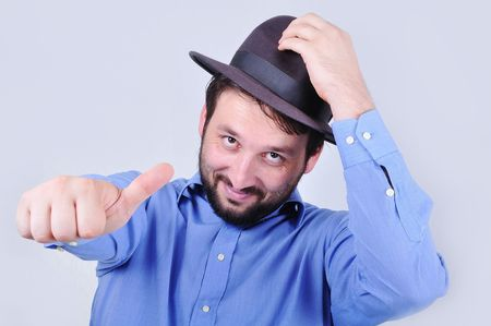 Young man with hat and pointing with his thumb up photo