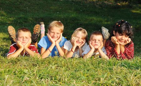 Children together, happiness on green meadow in summer time Stock Photo - 5495294
